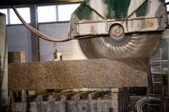 Granite processing in manufacturing. Cutting granite slab with a circular saw. Use of water for cooling. Industrial sawing of. Granite processing in royalty free stock photography