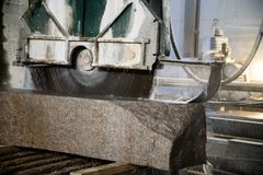Granite processing in manufacturing. Cutting granite slab with a circular saw. Use of water for cooling. Industrial sawing of. Granite processing in stock image