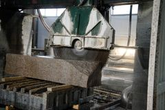 Granite processing in manufacturing. Cutting granite slab with a circular saw. Use of water for cooling. Industrial sawing of. Granite processing in royalty free stock image