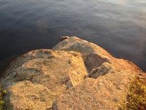 Granite rock face towering above a freshwater lake stock photos