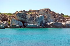 Granite rock face and turquoise waters Stock Images
