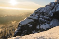 Granite rock in the winter forest at sunset stock images