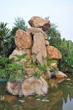 Granite rockery in pond water Royalty Free Stock Images