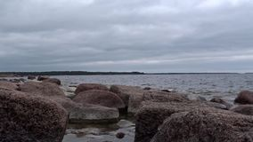 Granite rocks at the Finnish Baltic Coast. View over granite rocks to the gray Baltic Sea. The Finnish island of Emäsalo with typical woodland in the background stock footage