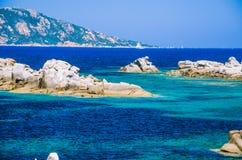 Granite rocks in sea, amazing azure water, white sailboat in background near Porto Pollo, Sardinia, Italy Royalty Free Stock Photos