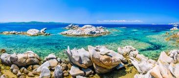 Granite rocks in sea, amazing azure water, white sailboats in background near Porto Pollo, Sardinia, Italy Stock Photos