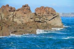 Granite rocks at seaside among waves Royalty Free Stock Images