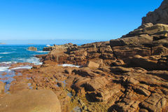 Granite rocks at seaside among waves Stock Photos