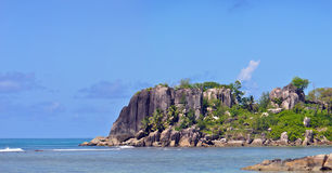 Granite rocks at the Seychelles. Some massive granit rocks at a beach on the Seychelles with palms an vegetation royalty free stock photo