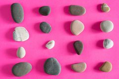 Granite smooth pebbles sea stones on pink background top view stock photos