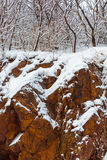 Granite and Snow. Wisconsin red granite rock and woods with December snow Royalty Free Stock Photography