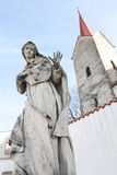 Granite statue of Virgin Mary with church tower Royalty Free Stock Photography