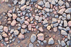 Granite stones on the earth. Granite stones on the wet earth a background Royalty Free Stock Photography