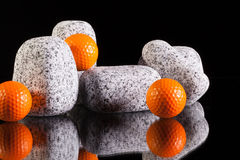 Granite stones and golf balls Royalty Free Stock Photography