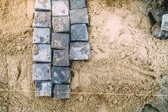 Granite stones on sand. Cobblestone blocks placement on sidewalk. Granite stones on sand path. Cobblestone blocks placement on sidewalk Stock Photo