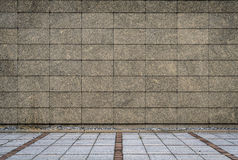 Granite tiles wall and concrete block pavement Royalty Free Stock Image