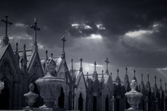 Granite tombs in the form of chapel. Many granite tombs in the form of chapel topped with crosses from an old european cemetery. Used infrared filter royalty free stock image