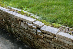 Granite wall made of bricks and fresh lawn grass shot with place for text on a sunny day Royalty Free Stock Photo