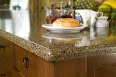 Granitekitchen counter top with breakfast. Granite kitchen counter top with breakfast, croissant, fruits and jam stock images