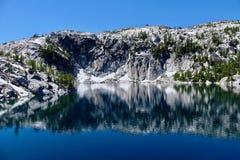 Granitfelsen und -reflexionen im ruhigen Wasser Lizenzfreies Stockbild