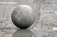 Granitkugel auf einer Fahrbahn. Stockfotografie