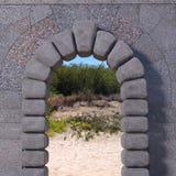Granitport med väggen och sandigt landskap royaltyfri fotografi