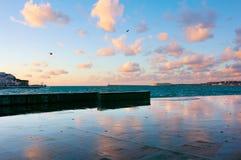 Granitsjösida med reflexion av moln på solnedgången royaltyfria bilder