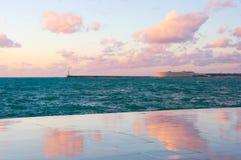 Granitsjösida med reflexion av moln på solnedgången arkivbild