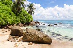 Granitstenar på den vita sandiga stranden med en vagga och himmel med moln Royaltyfri Foto