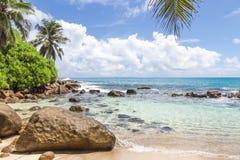 Granitstenar på den vita sandiga stranden med en vagga och himmel med moln Royaltyfria Foton
