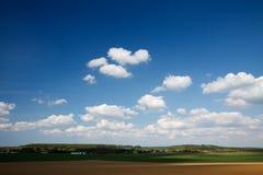 Granja bajo el cielo brillante con las pequeñas nubes foto de archivo libre de regalías