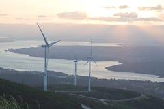 Granja de la turbina de viento con los rayos de la luz en la puesta del sol Fotos de archivo libres de regalías