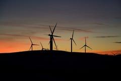 Granja de la turbina de viento en la puesta del sol Fotografía de archivo libre de regalías
