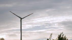 Granja de la turbina de viento, generadores de la energía eléctrica, en campo en fondo del cielo nublado metrajes