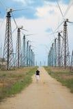 Granja de las turbinas de viento y persona que recorre Fotografía de archivo