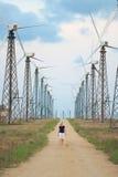 Granja de las turbinas de viento y persona que recorre Imagenes de archivo