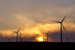 Granja del molino de viento en la puesta del sol Fotos de archivo libres de regalías