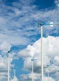 Granja del molino de viento para la energía limpia alternativa con las nubes y el azul foto de archivo