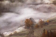 Granja en las colinas en las montañas Ondas de la niebla en un bosque Imagenes de archivo