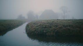 Granja holandesa de niebla en un paisaje verde y mojado del prado en el invierno Con la caña en el primero plano metrajes