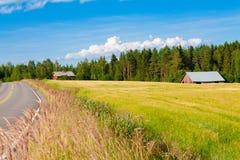 Granja roja con el camino, el cielo azul y el campo verde imagenes de archivo