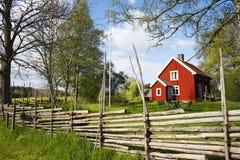 Granja roja vieja en un paisaje rural Imagenes de archivo