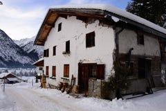 Granja vieja con el paisaje de madera y las montañas del invierno Fotografía de archivo