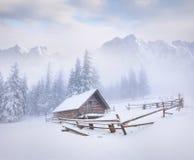 Granja vieja en montañas de niebla del invierno Imagenes de archivo