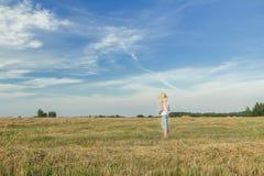 Granjero adolescente que se coloca en campo cosechado Imagen de archivo