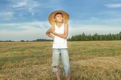 Granjero adolescente que se coloca en campo cosechado Foto de archivo libre de regalías