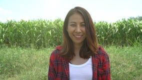 Granjero alegre y empresario de sexo femenino asiáticos que presentan en la cosecha del maíz y que sonríen en el concepto de la c almacen de metraje de vídeo