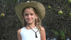Granjero Child en el manzanar, muchacha del país que mira la cámara sonriendo, yarda 4K almacen de video