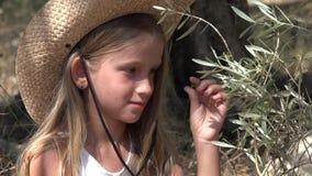 Granjero Child Studying Olive Fruits en huerta, niña que juega por el árbol 4K