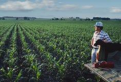 Granjero con el perro en el campo de maíz